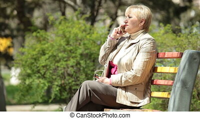 woman talking on phone - Cheerful senior woman using phone...