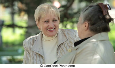 Senior best female friends - Cheerful senior woman speaks...