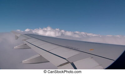 Climbing Airplane - View of the clouds as the airplane...