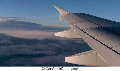Flight above the Clouds - View of airplane wing above the...