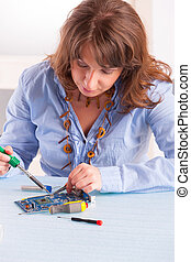 Soldering - Woman using soldering tool for the computer...