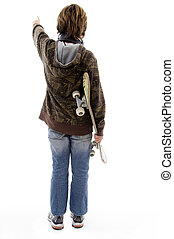 back pose of pointing boy holding skateboard on an isolated...