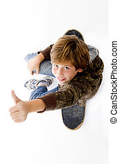 top view of boy sitting on skateboard and showing thumbs up