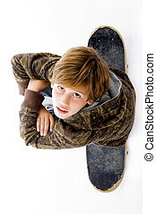 top view of boy sitting on skateboard on an isolated white...