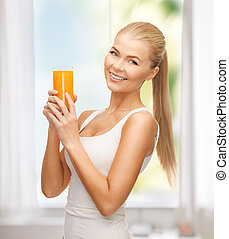 woman holding glass of orange juice - young woman holding...