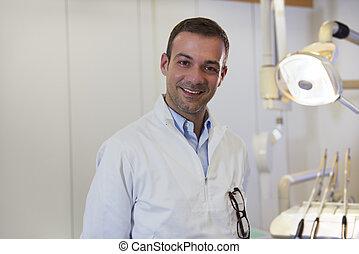 Portrait of happy caucasian dentist smiling at camera