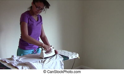 Ironing - Young woman ironing blouse