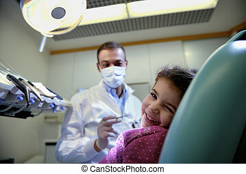 young girl lying on couch in dentist studio looking at...