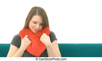 Woman cuddling with a heart pillow