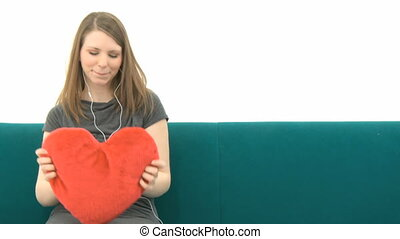 Pretty Woman listening to music and cuddling with a heart pillow