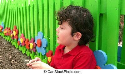 Little Boy Posing Outside by Fence