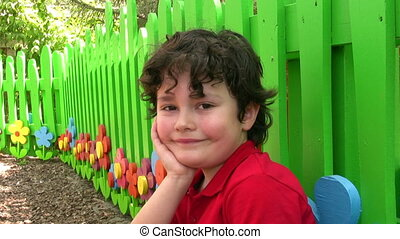Little Boy Posing Outside by Fence