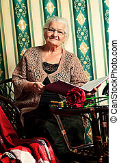 telling tales - Portrait of a smiling senior woman reading a...