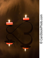 candles flare and candleholder reflection in form of heart -...