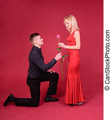 a man with rose flower and a woman against red background - happy couple or proposal  concept