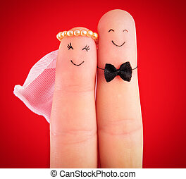 newlyweds hug painted at fingers isolated on red background...
