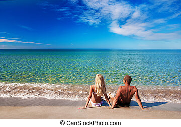 young couple sitting on the sea sand beach and look at sky -...