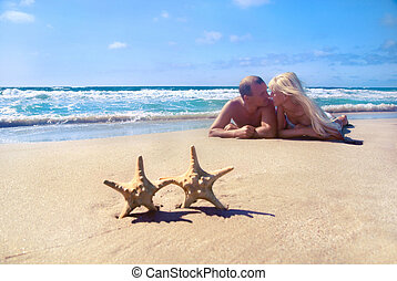 loving couple - blonde woman and man - lying on the sea sand beach against starfishs and look at each other
