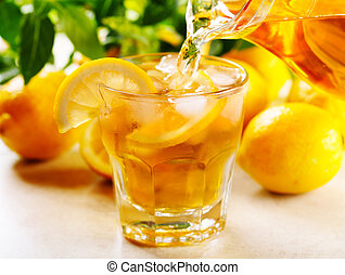 pouring ice tea into glass with slices of lemon