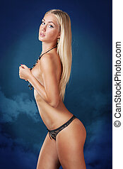 Cute blond woman standing topless covering breast in panties...