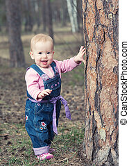 happy baby girl in jeans jumpsuit stands on legs near a tree in the park outdoors