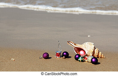 Christmas balls and seashell on the beach