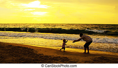 father and daughter playing together on the beach at sunset