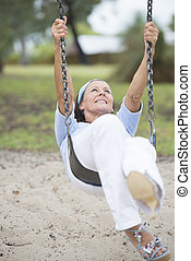 Joyful senior woman on swing active retirement - Portrait...