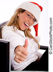 side view of smiling manager with christmas hat showing thumb up in an office