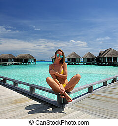 Woman on a beach jetty at Maldives - Woman on a tropical...