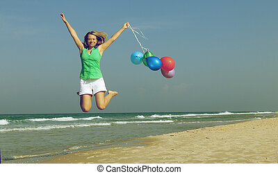 Beautiful girl with a balloons on the beach. Old style colours.