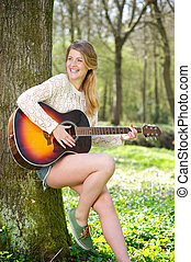 Beautiful young woman smiling with guitar outdoors