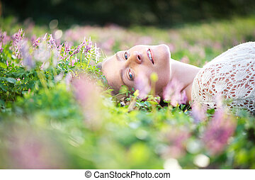 Beautiful young woman lying on grass with spring flowers