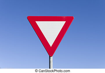 give way traffic sign against a clear blue sky