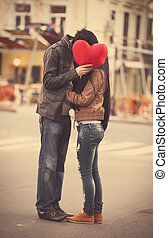 Young couple kissing on the street - Young couple with shape...