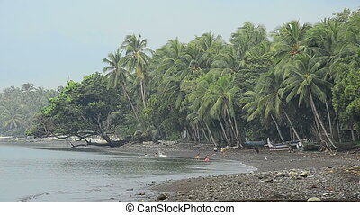 balinesian people bathing in ocean under palms