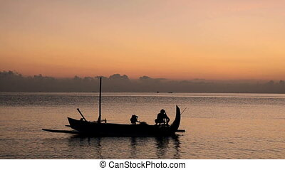 fisherman in Bali at sunrise on his Jukung