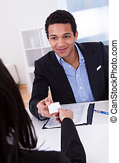 Businesswoman Offering Visiting Card To Man In Office