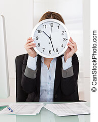 Businesswoman Holding Clock In Front Of Her Face In Office