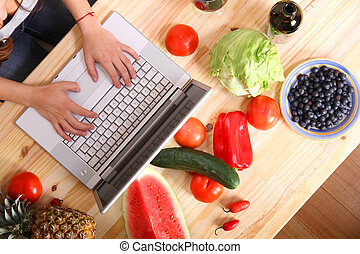 Woman using a Laptop while cooking - A young woman using a...