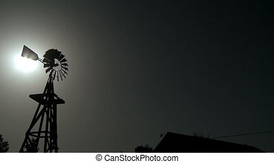 Vintage Windmill rotating in the wind with the sun shining...