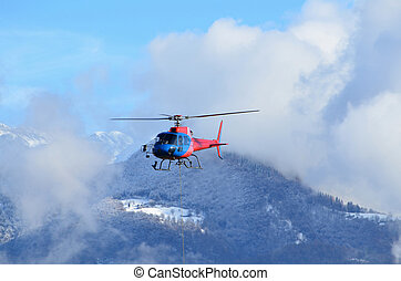 Helicopter flying over the alps in winter