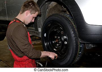 Reifenwechsel - Techniker prueft Reifendruck