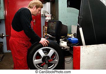 Kfz-Techniker montiert Reifen - Mechaniker montiert...