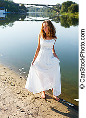 Young cheerful girl bride walk barefoot the sunny coast of...