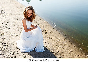 Elegant smiling girl bride in a white dress on a sandy river...