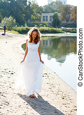 Young girl bride walk barefoot the sunny coast of the river...