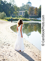 Young girl bride in a white dress on the sunny coast of the...