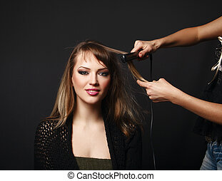 young woman at hairdresser, dark background