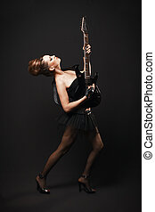 Rock female with guitar over dark background